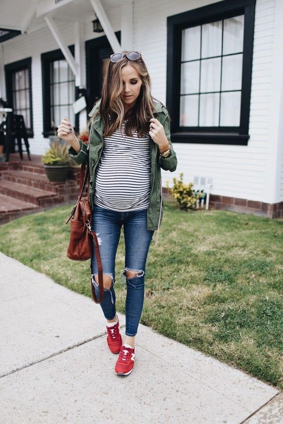 casual spring outfit with ripped denim, red chucks, a striped top and an army green jacket
