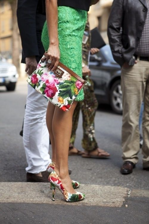 a black top, a green lace knee skirt and floral shoes and a matching clutch