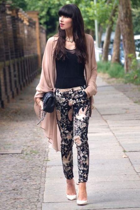 a black top, black and blush floral pants, white shoes and a blush cardigan