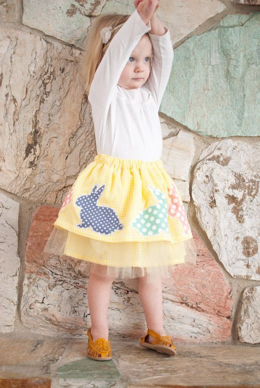 cute little girl look with a white long sleeve, a yellow skirt with bunnies and ocher sandals