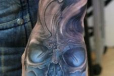 03 black and blue skull tattoo on a hand and arm