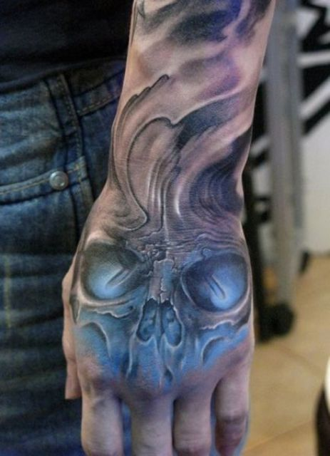 black and blue skull tattoo on a hand and arm