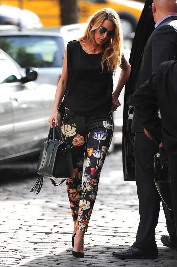 a black top, black floral pants and black heels