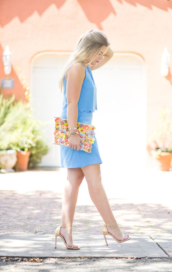 a blue scalloped top and a mini skirt, nude heels and a floral applique clutch