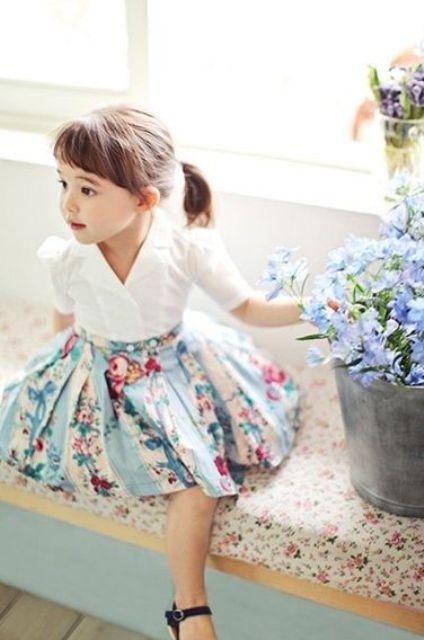 a blue floral skirt, a white shirt with a V-neckline