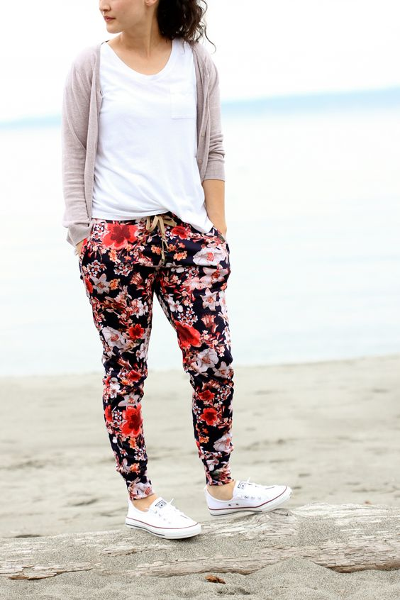 a white tee, floral pants, a blush cardigan and white sneakers
