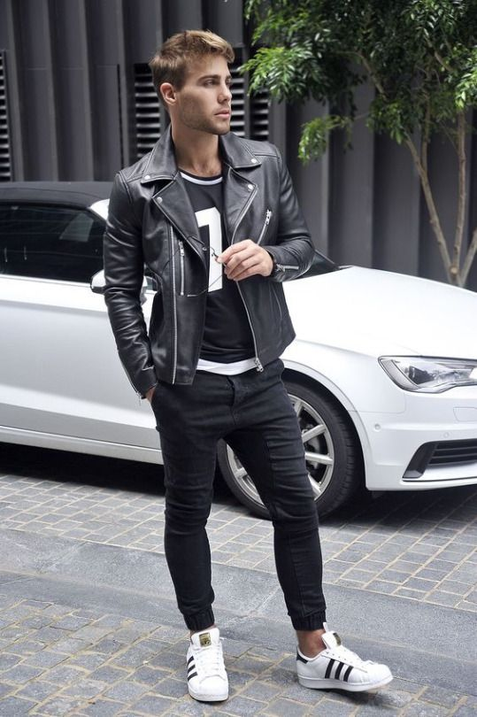 black jeans, a sporty print tee, a black moto jacket and white chucks