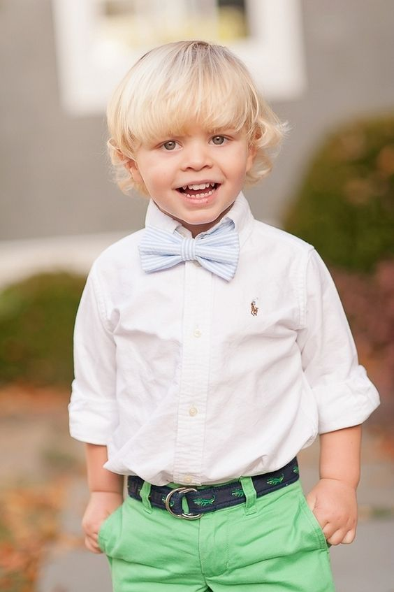 green pants, a white shirt and a blue striped bow tie