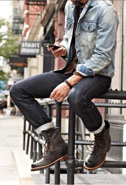 a distressed denim jacket, black jeans, a shirt and brown boots