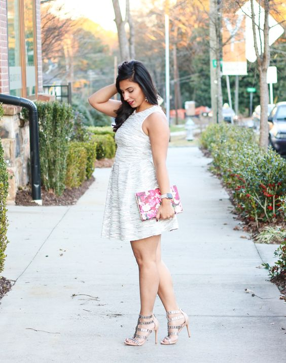 a metallic grey dress, a floral clutch, silver strap heels