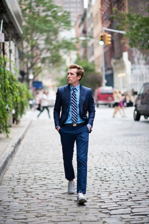 a navy suit, a blue shirt, a striped tie and sneakers