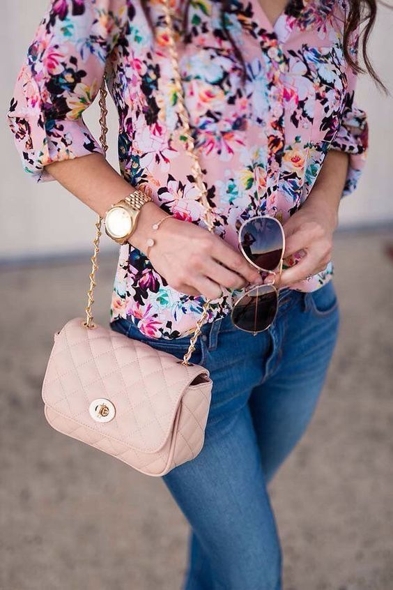 a pink floral blouse, blue skinnies and a pink crossbody