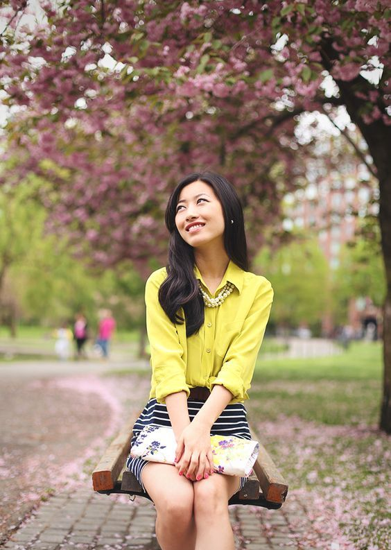 a striped mini skirt, a yellow blouse  and a floral clutch