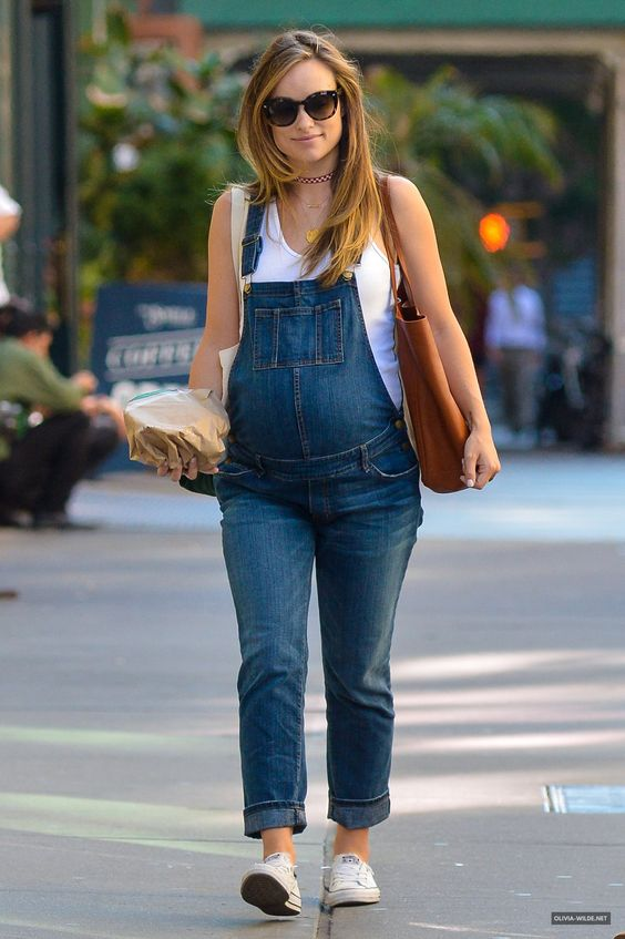 simple maternity outfit with a denim overall, white chucks and a white top for a cozy feel