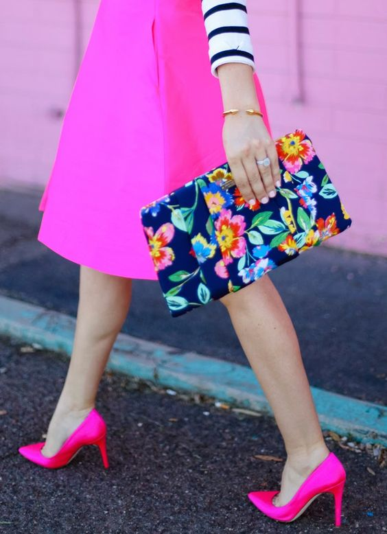 a striped shirt, a hot pink skirt and shoes and a bold floral clutch