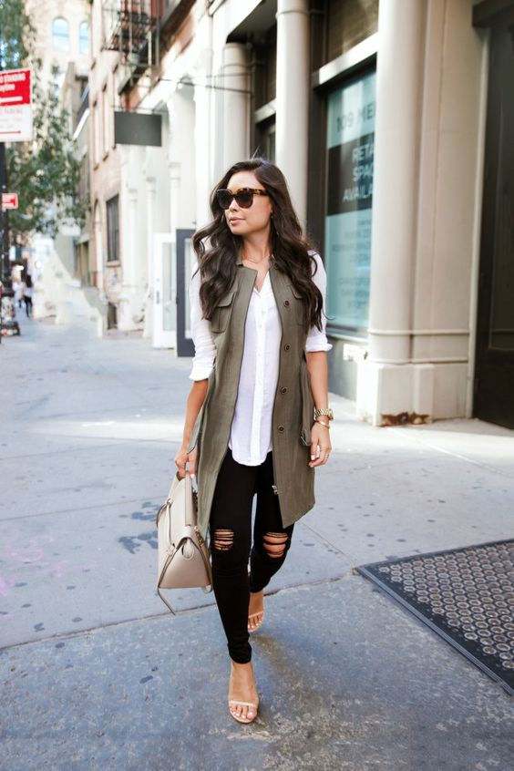 a white shirt, black ripped jeans, nude ankle strap heeled sandals and a khaki long vest