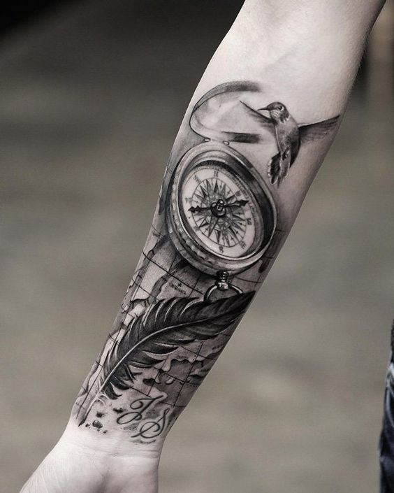 compass and feather forearm tattoo with a bird