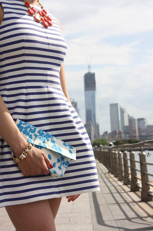 a striped navy and white mini dress with a statement necklace and a small floral clutch