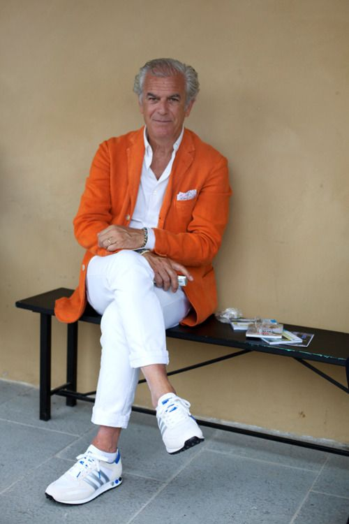 a white shirt, white jeans, an orange jacket and white chucks