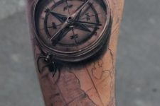 11 map and 3D compass tattoo on an arm with black ink