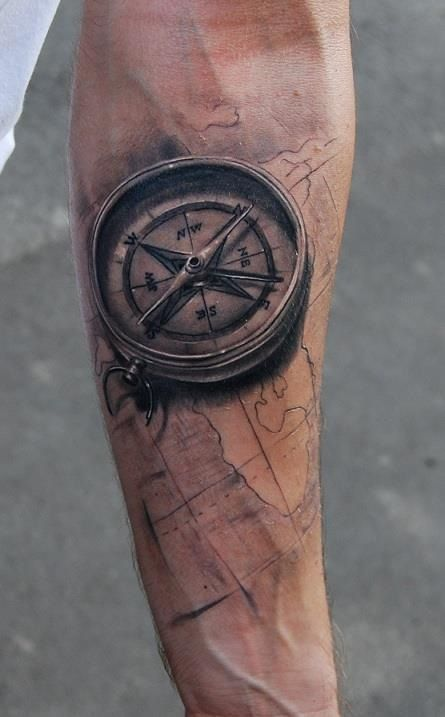 map and 3D compass tattoo on an arm with black ink