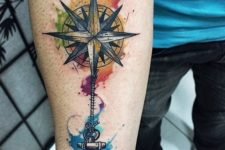 12 a colorful compass and anchor tattoo on an arm
