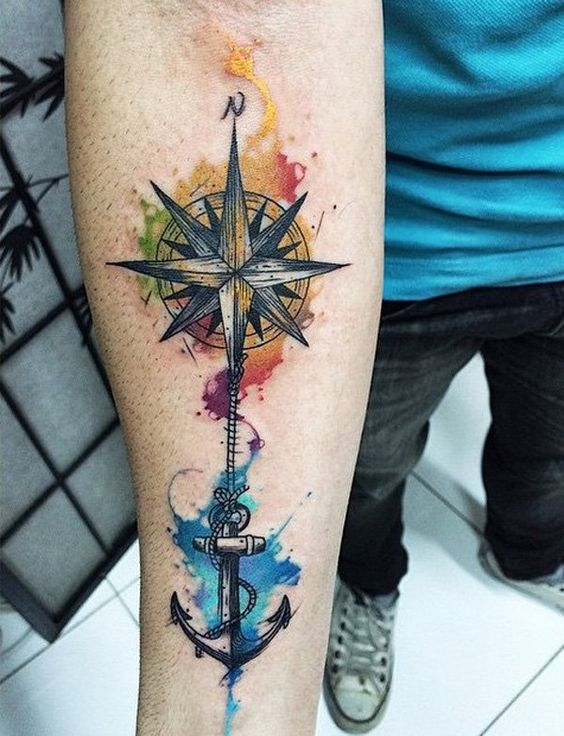 a colorful compass and anchor tattoo on an arm