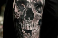 13 a skull tattoo on an arm with a chaos symbol