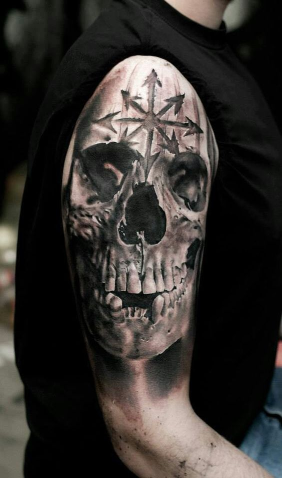 a skull tattoo on an arm with a chaos symbol