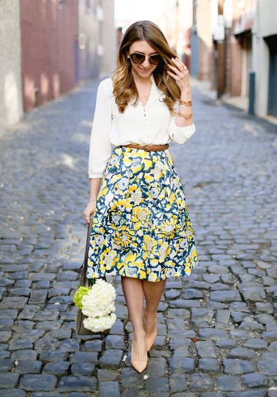 a white shirt, a bold yellow and green knee skirt and nude pumps