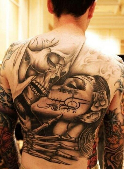 a whole back tattoo with a skull and a girl kissing