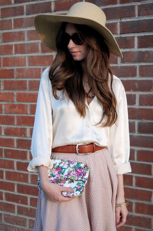 an ivory blouse, a blush polka dot skirt with a leather belt and a small floral clutch