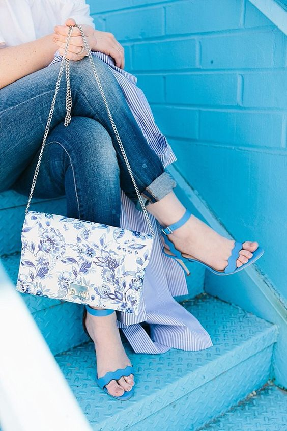a white shirt, blue jeans, bold blue heeled sandals and a flower crossbody bag
