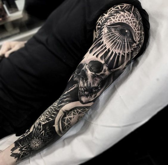 a whole sleeve tattoo with a skull and an eye