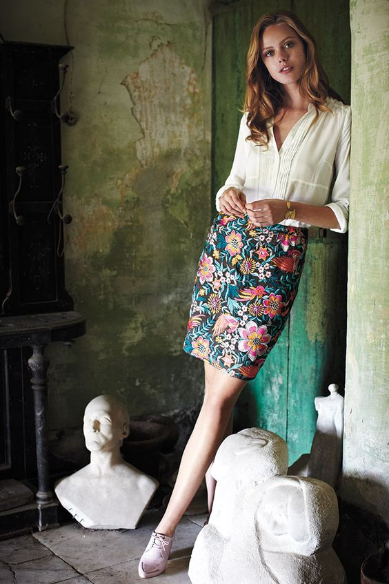 an ivory v neck blouse, a floral over the knee skirt and blush shoes