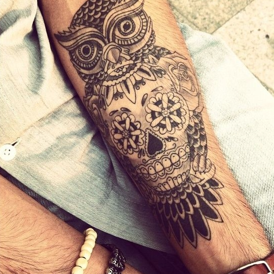 an owl image and a skull spotted in it stomach on the arm