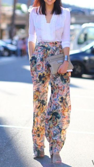 a white blouse with half sleeves, wide floral pants and grey suede shoes