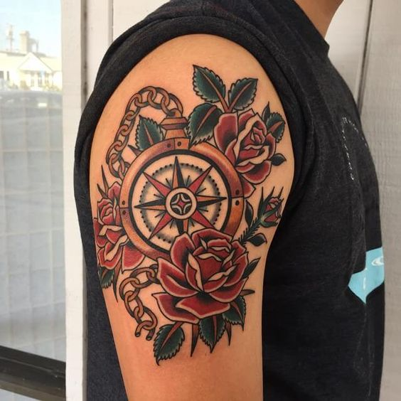 colorful compass tattoo with roses on an arm