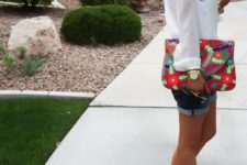 17 denim shorts, a white blouse with pompom trims and grey peep toe booties and a bold floral clutch