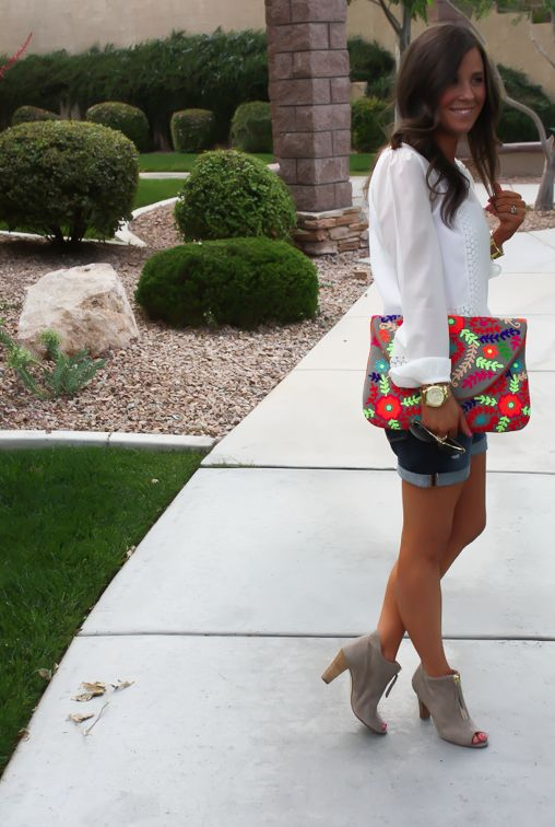 denim shorts, a white blouse with pompom trims and grey peep toe booties and a bold floral clutch