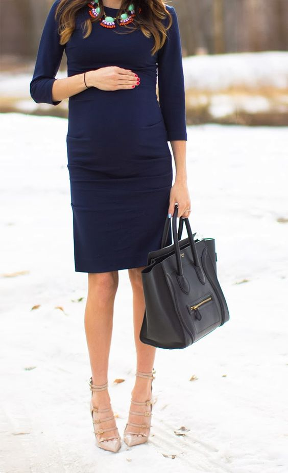 elegant pregnant woman in navy dress and nude heels