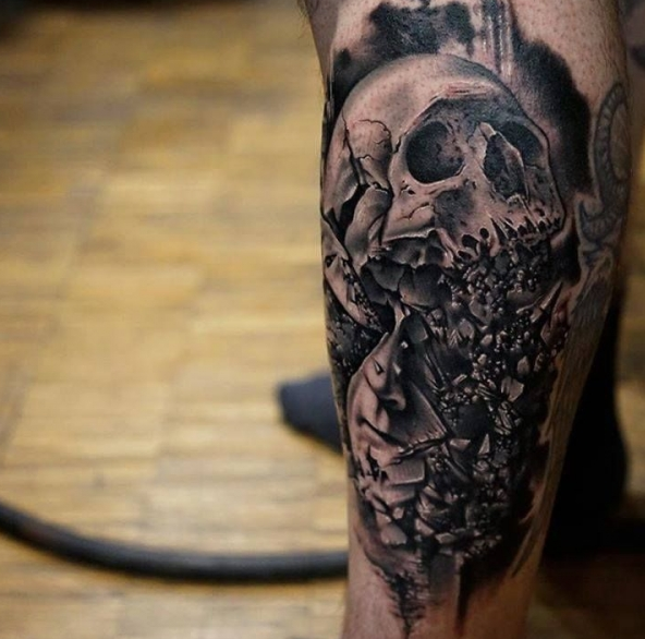 black and white skull tattoo on a leg