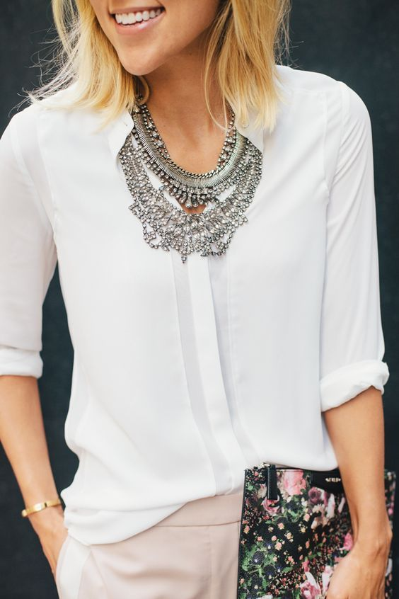blush pants, a white blouse, a statement necklace and a floral bag
