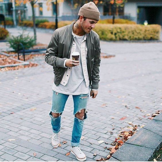 ripped jeans, a grey tee and a denim jacket, an olive green jacket and white Converse