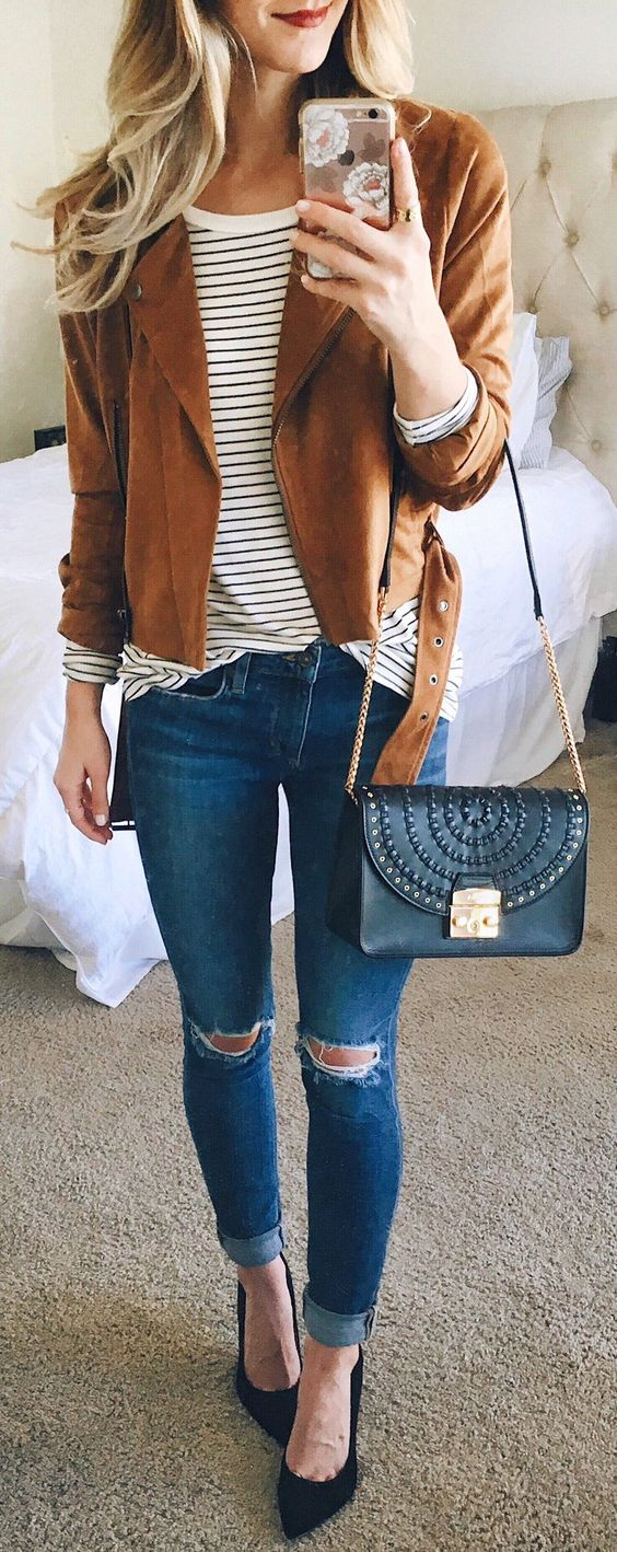stylish look with ripped skinnies, a striped teeem a brown leather jacket and black heels