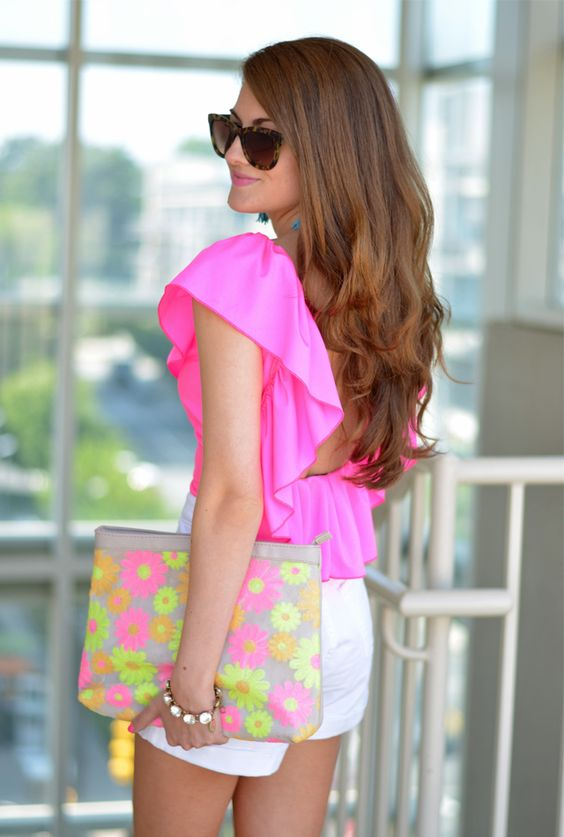 white shorts, a hot pink ruffled top and a floral clutch