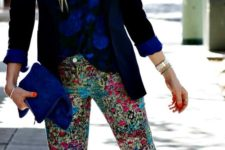 21 a bold blue floral shirt, a black jacket, colroful floral pants and bold blue heels