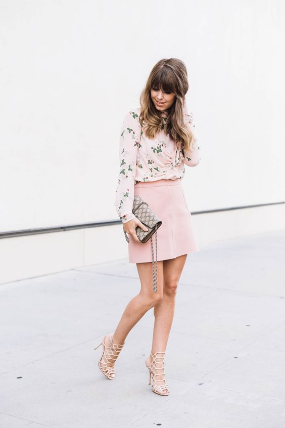 a delicate floral blouse, a pink mini and lace up heeled sandals
