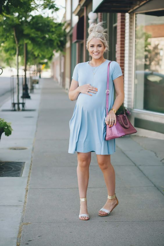 a light blue dress, flat sandalds and a pink bag