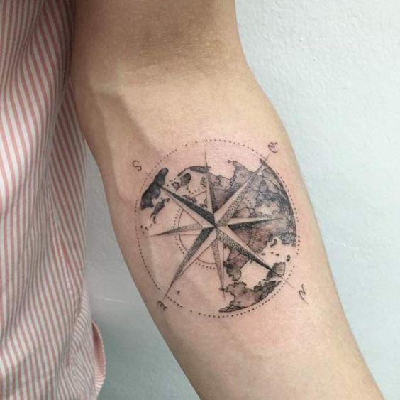 nautical globe compass tattoo on an arm